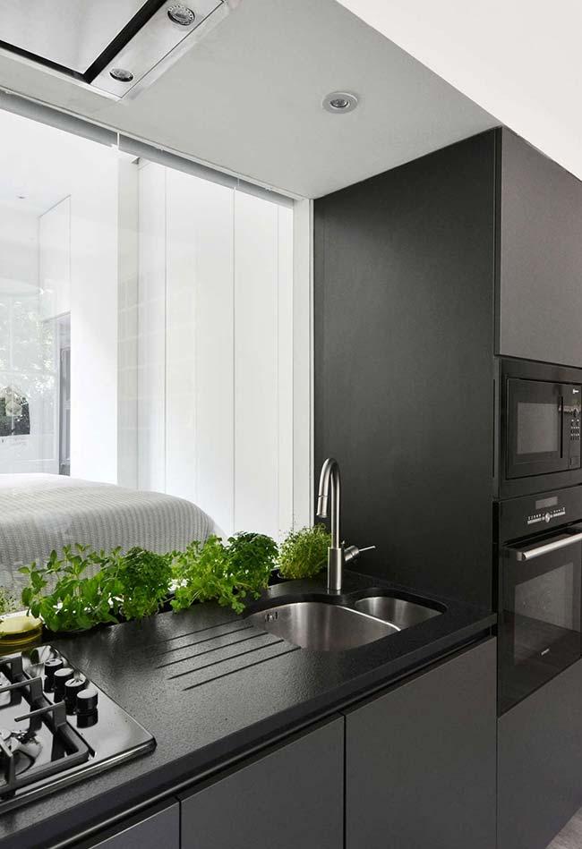 Cozinha preta com horta na bancada da pia