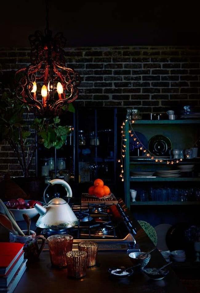 Cozinha dark com um lustre de influência gótica