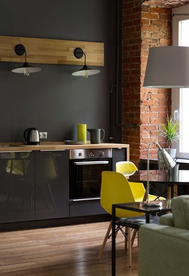 Amarelo das cadeiras reforça o estilo rústico dessa cozinha preta