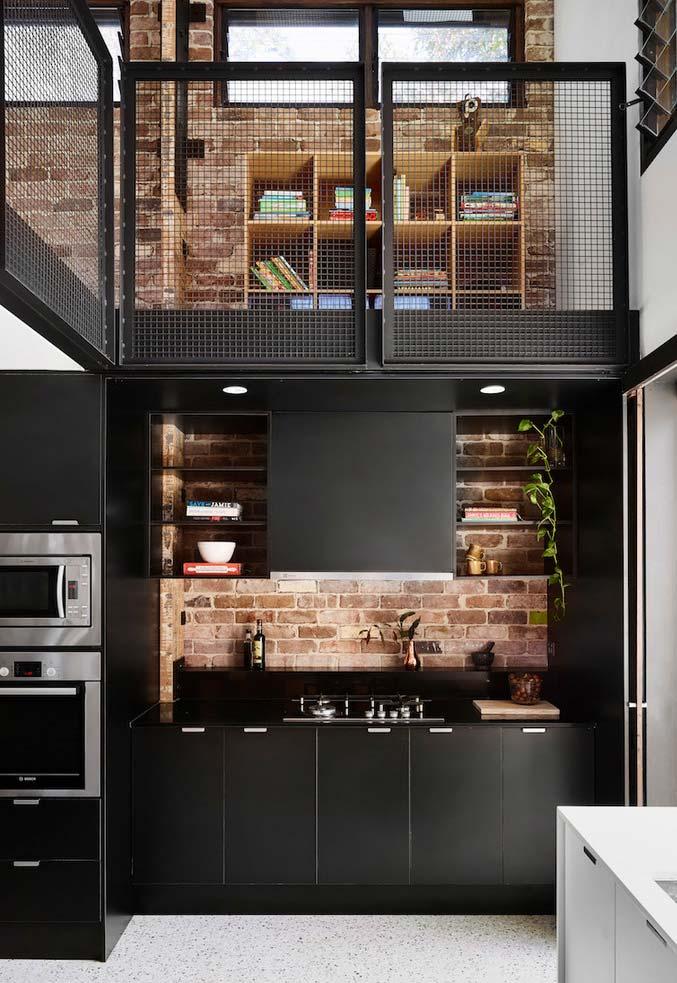 Cozinha preta com tijolinhos aparentes ao fundo