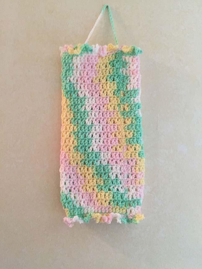 Um colorido suave e harmônico forma esse porta papel higiênico de crochê