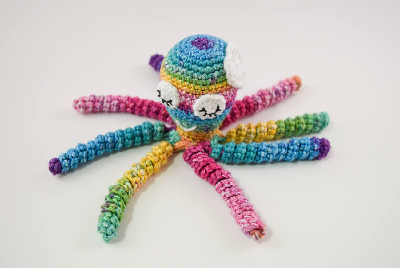 Polvo de crochê colorido com uma flor branca na cabeça