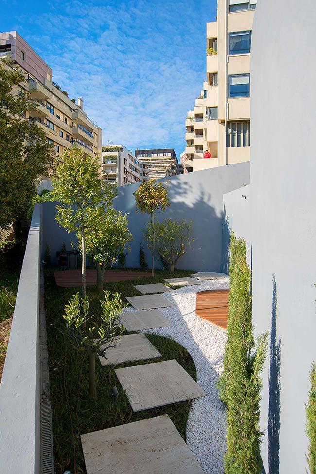 Jardim pequeno em prédio simples com gramado e árvores