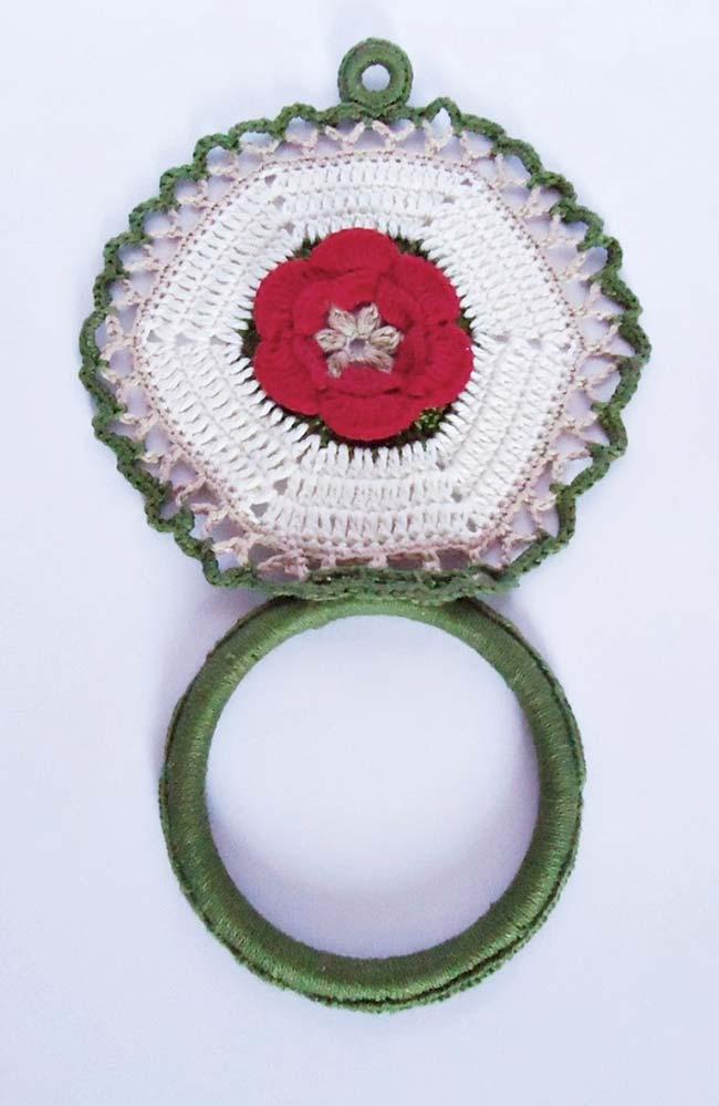 Flor vermelha se destaca em meio ao porta pano branco e verde