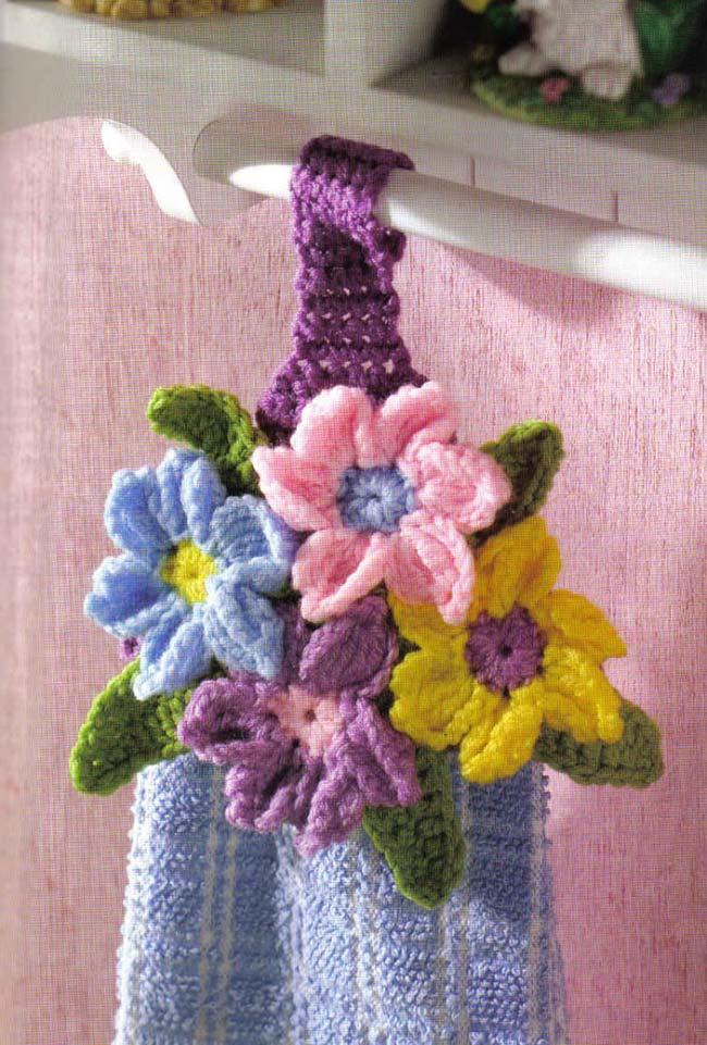 Flores coloridas do porta pano de prato de crochê embelezam a cozinha