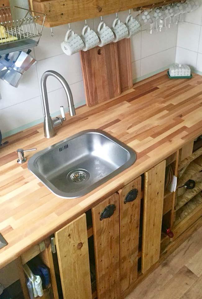 Bancada de madeira e armários de pallet na cozinha
