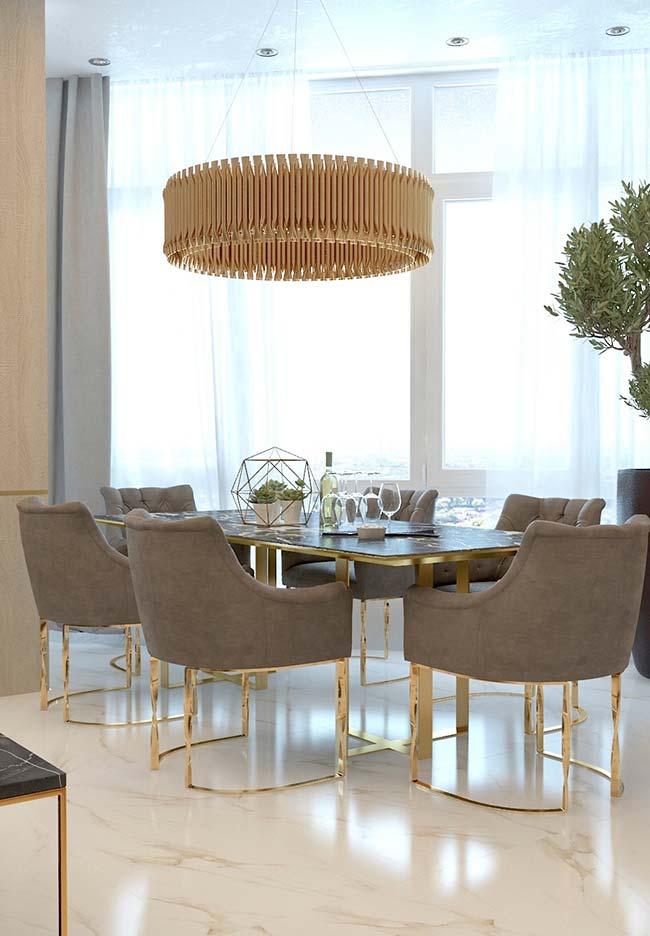 Mármore Calacatta Oro no piso e detalhes dourados nos móveis