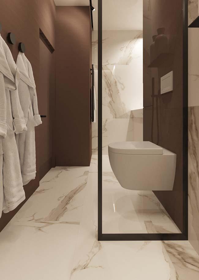 Mármore Calacatta Oro contrastando com o tom terroso da parede do banheiro