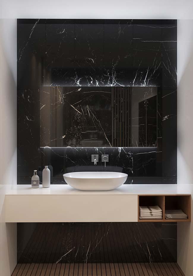 Todo charme e elegância do mármore preto emprestado para esse banheiro de fundo branco