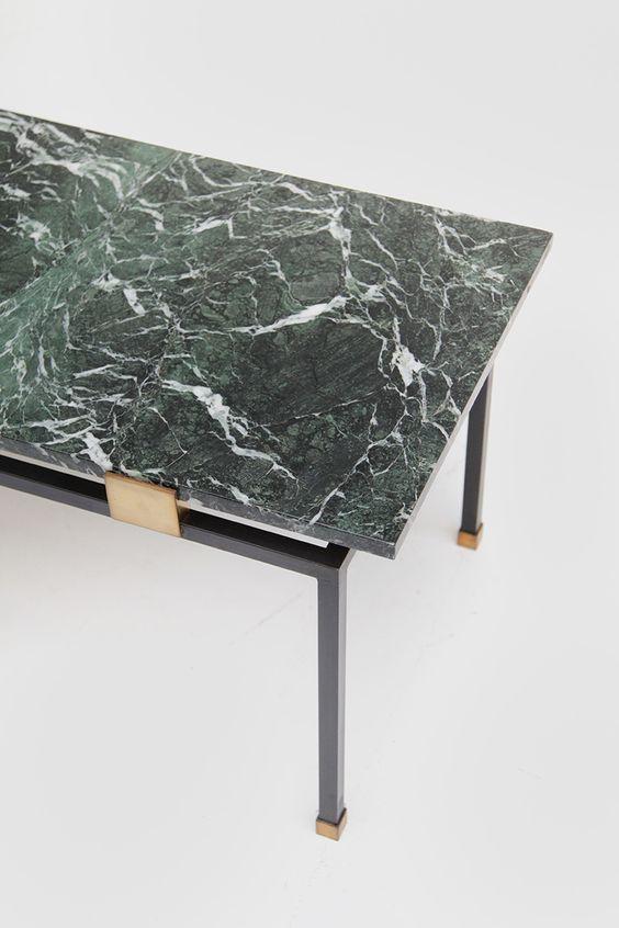 Mesa com tampo de mármore verde; veios marcantes parecem dar movimento a pedra