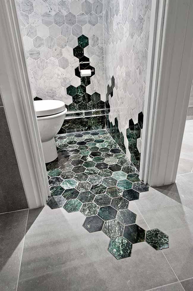 Hexágonos de mármore verde e mármore branco decoram esse banheiro