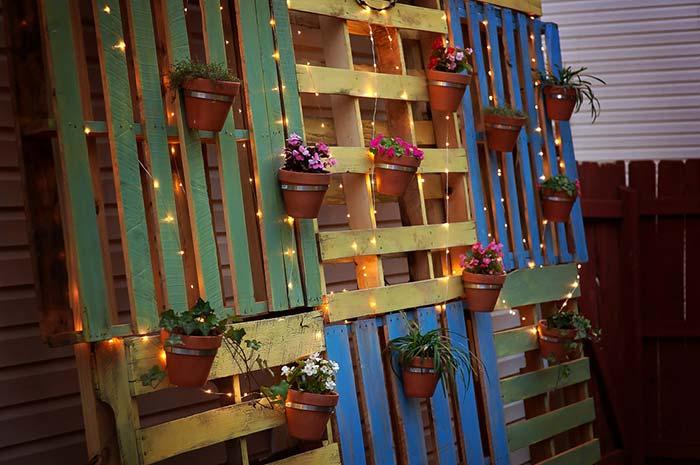 Pallets coloridos recostados na parede sustentam os vasos de plantas