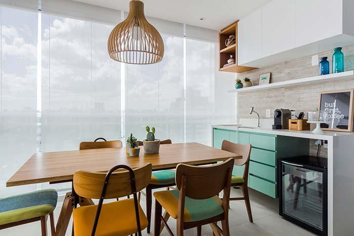 Cadeiras diferentes, na cor e no design, compõe a mesa dessa varanda gourmet