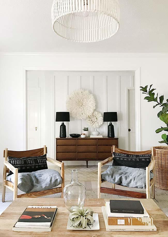 O par de abajures preto se destaca nessa sala de decoração predominante branca
