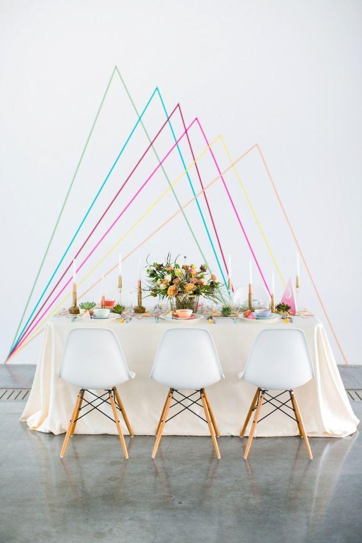 Decoração de casamento faça você mesmo: velas, flores e uma parede com linhas coloridas atrás