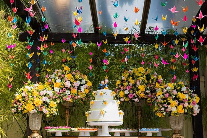 Tsuru, pássaro de origami, decora a região onde fica a mesa do bolo do casamento