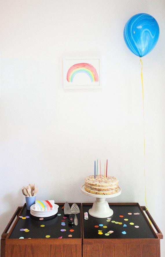 Balão, bolinho e alguns confetes na mesa do mesversário de bebê