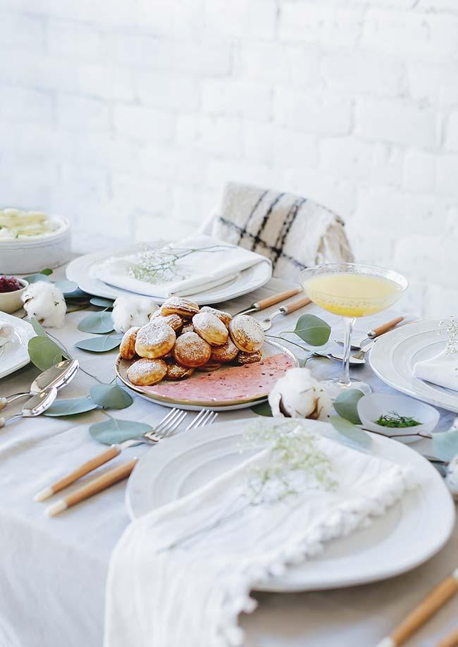 Uma mesa simples, com toalha e louças brancas, ganha um charme a mais com os galhos de folhas naturais