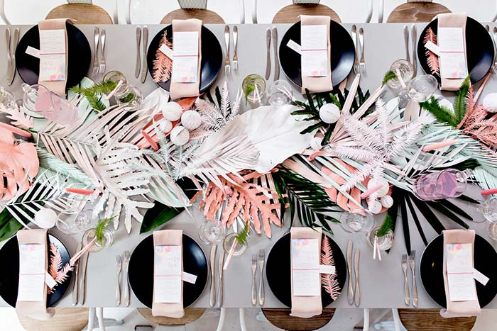 Guardanapos e menus sobre os pratos na mesa posta
