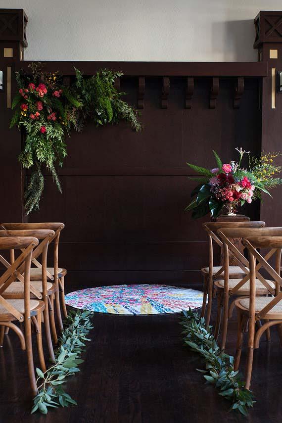 Arranjos simples de flores e ramos de folhas decoram a cerimônia desse casamento