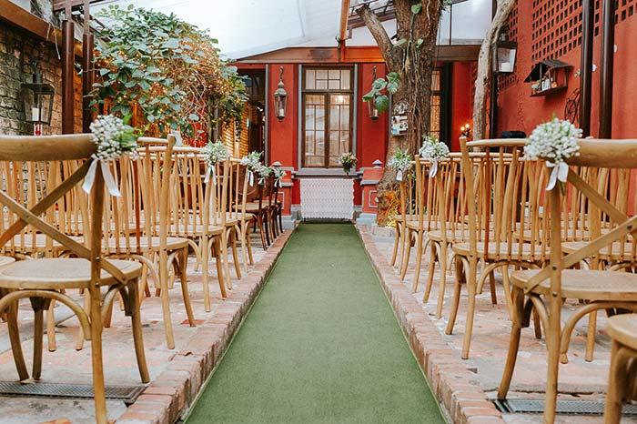 Pequenos buquês de flores brancas decoram as cadeiras para a cerimônia
