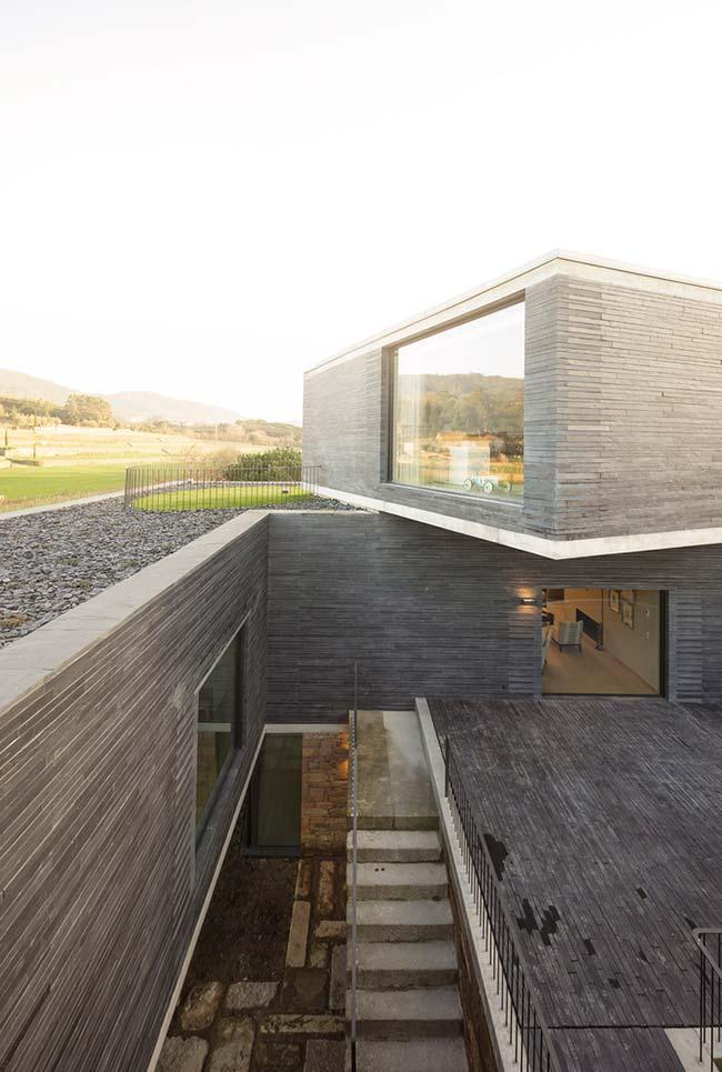Nesse projeto de arquitetura moderna, o muro de arrimo fica na parte interna da construção