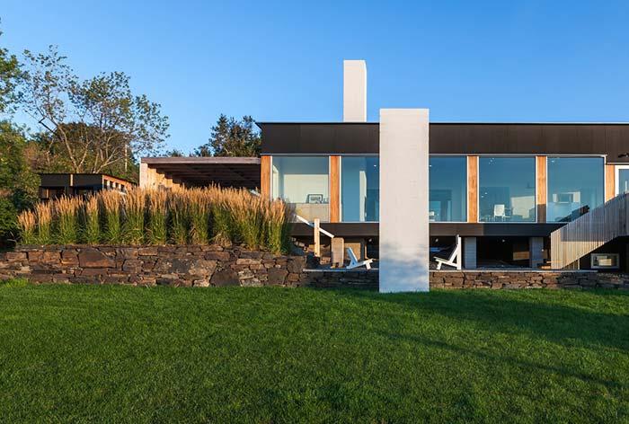 Muro de arrimo de pedras faz um lindo contraste com o quintal gramado