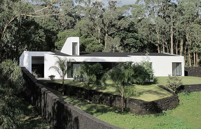 A casa de estilo moderno optou por um muro de arrimo rústico de pedras