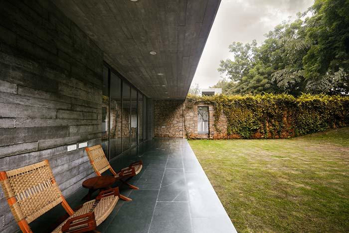 Para a casa de tons escuros, um muro de arrimo de pedras em cor de barro e plantas trepadeiras