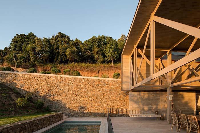 Casa de madeira e muro de arrimo de pedras