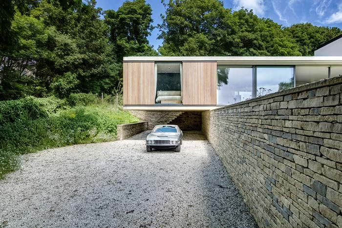 Muro de arrimo de pedras ajuda a sustentar a casa de estilo moderno