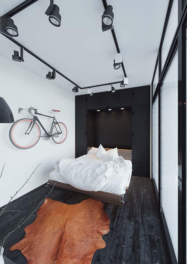A parede de cimento queimado branco foi decorada com uma bicicleta