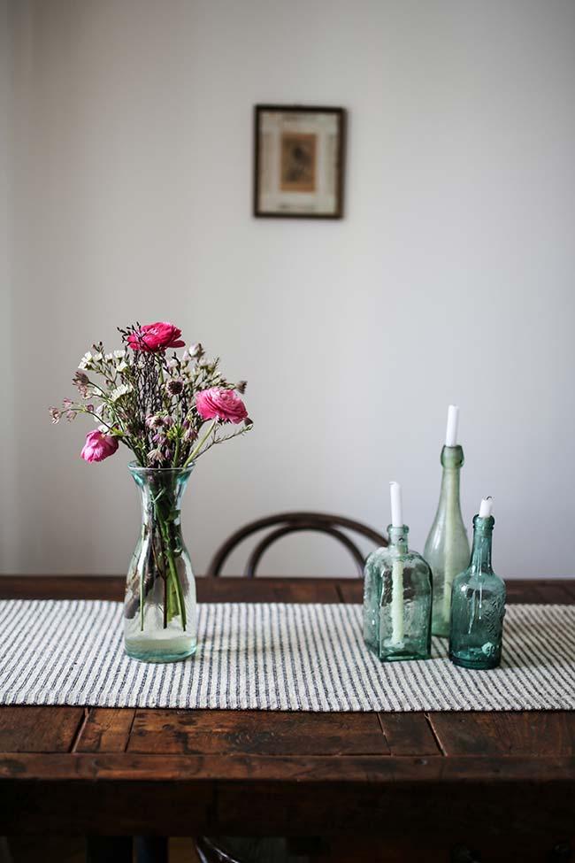 Velas dentro das garrafas de vidro e um arranjo simples de rosas