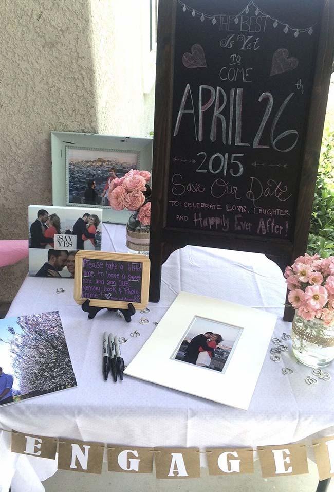 Em um cantinho da festa, uma mesa decorada com os bons momentos vividos pelo casal e o convite para a cerimônia de casamento que acontecerá em breve