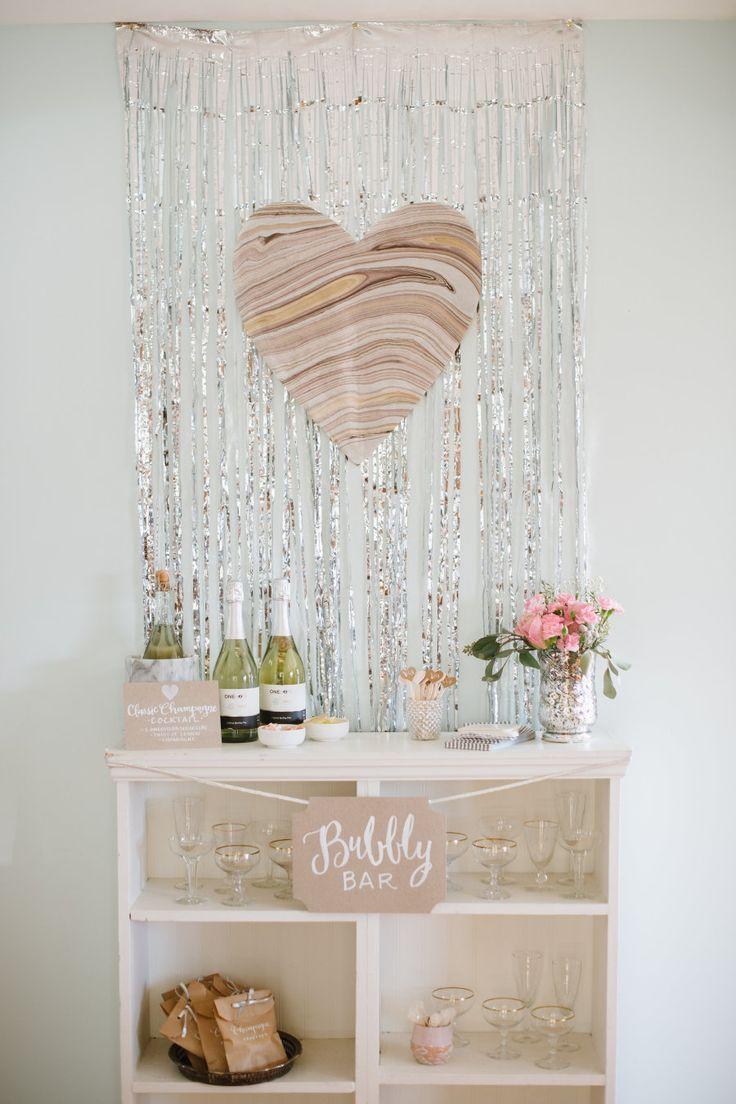 Um barzinho simples para os convidados se servirem decorado com tiras de fita metálica e coração de papel