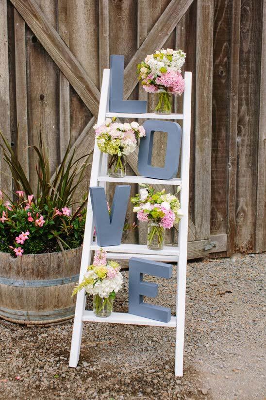 Festa de noivado simples: escadinha de madeira decorada com a palavra amor e vasinhos de flores