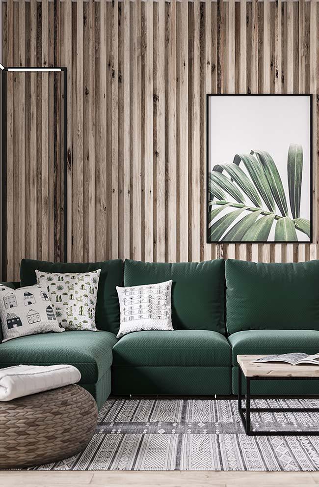 Sofá verde escuro realça a base rústica e de elementos naturais da sala de estar decorada