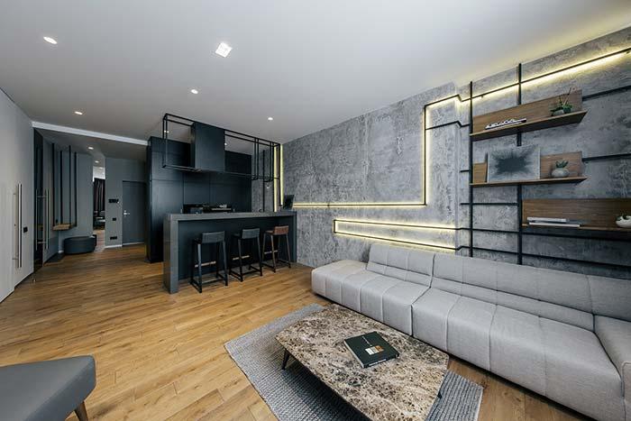 Piso de madeira, parede de cimento queimado e uma iluminação diferenciada para completar a decor da sala de estar