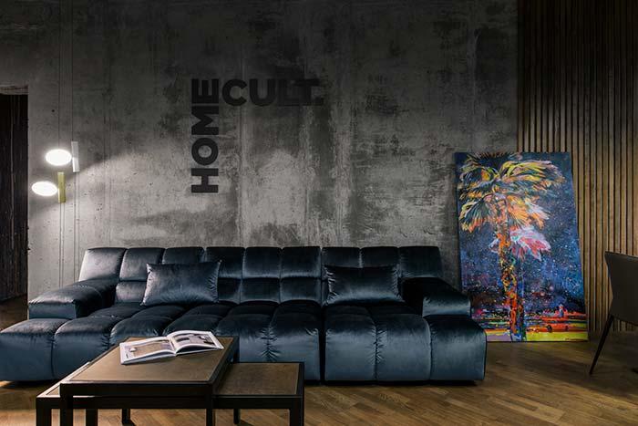Sala de estar decorada: o sofá de veludo em contraponto com a parede de cimento queimado são puro charme e sofisticação