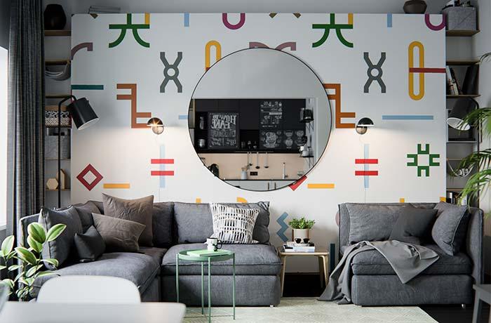 Espelho redondo sobre o papel de parede revela a integração entre os ambientes