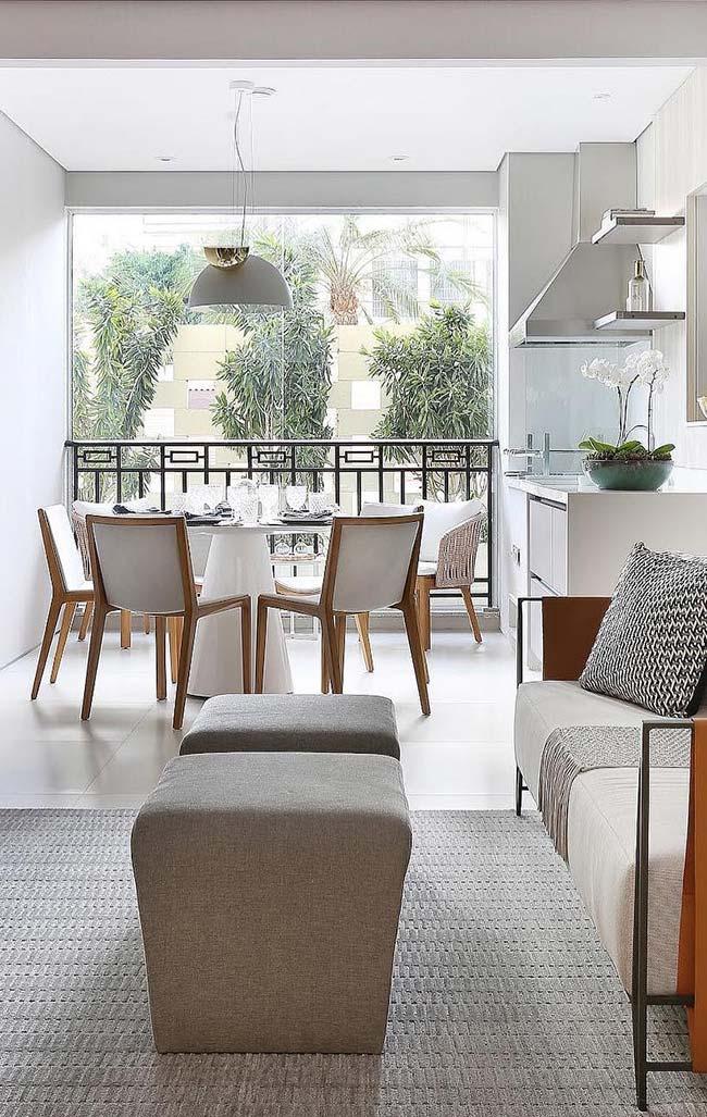Decoração clean de cores claras engloba a sala de estar, sala de jantar e varanda desse apartamento decorado