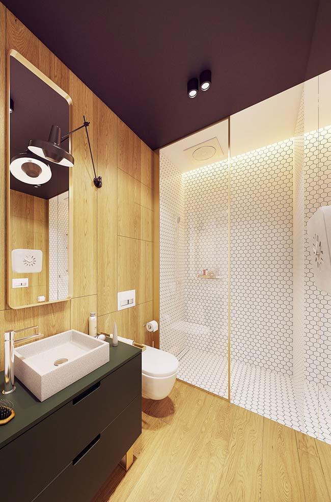 Apartamento decorado: teto de cor escura deixa o banheiro com um aspecto mais intimista e aconchegante; o painel amadeirado favorece essa proposta