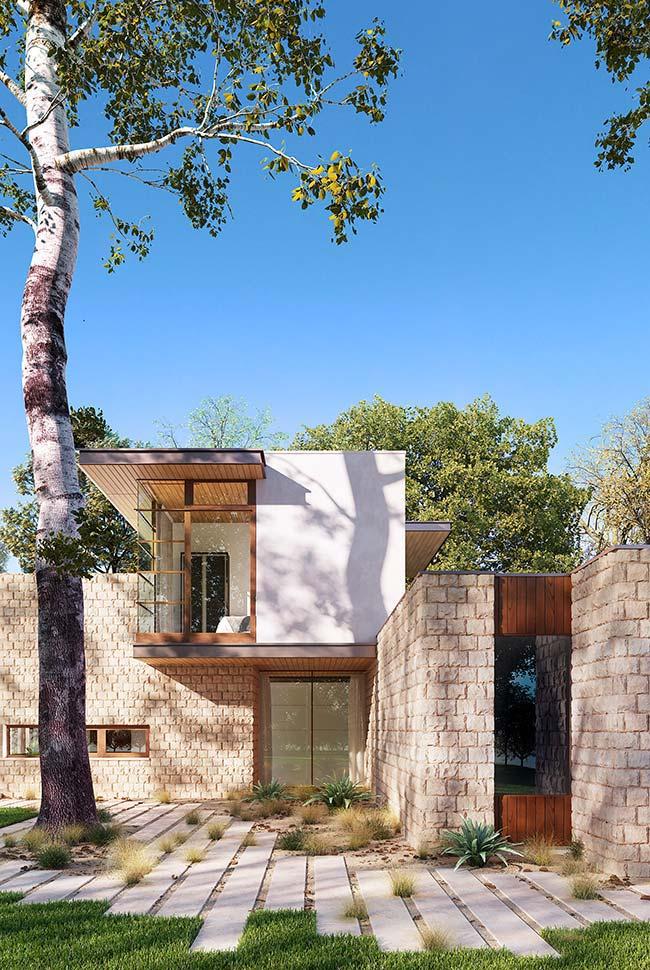Nessa casa, as pedras revestem os muros e foram combinadas ao vidro e a madeira