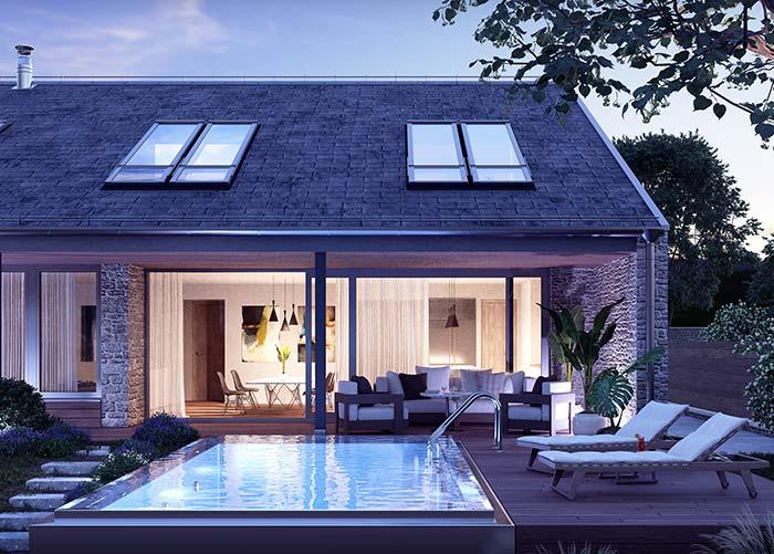 Casa com piscina optou por uma fachada de pedra para garantir um visual mais despojado e natural