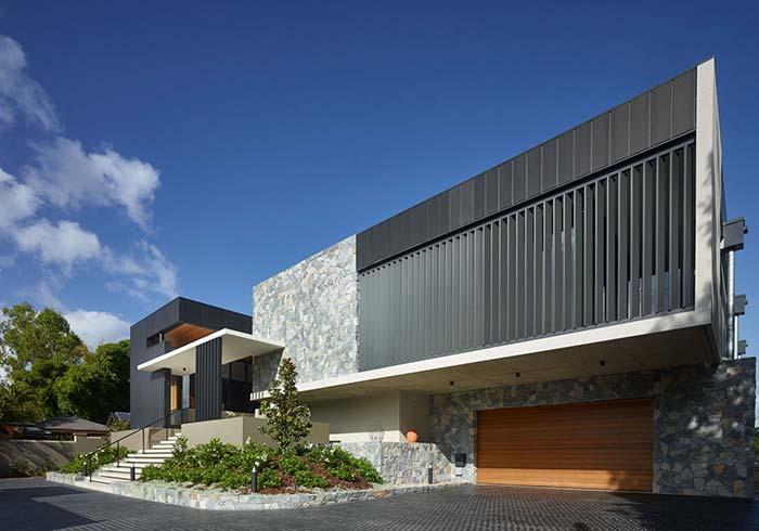 O tom acinzentado das pedras continua nos metais e na pintura da fachada dessa casa