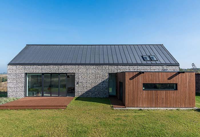 Uma fachada bem diferente: nessa casa, destacam-se os gabiões de pedra, uma estrutura metálica semelhante a uma gaiola cheia de pedra