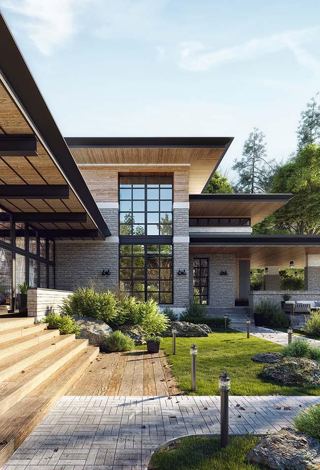 A fachada de casa com pedra grande foi dividida entre pedras e madeira