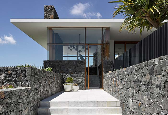 Pedras cinzas criam uma bela combinação com o branco do teto na fachada de casa com pedra