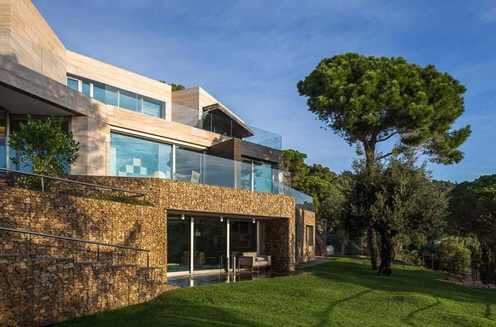 Gabiões de pedra ferro decoram toda essa enorme fachada de casa com pedra