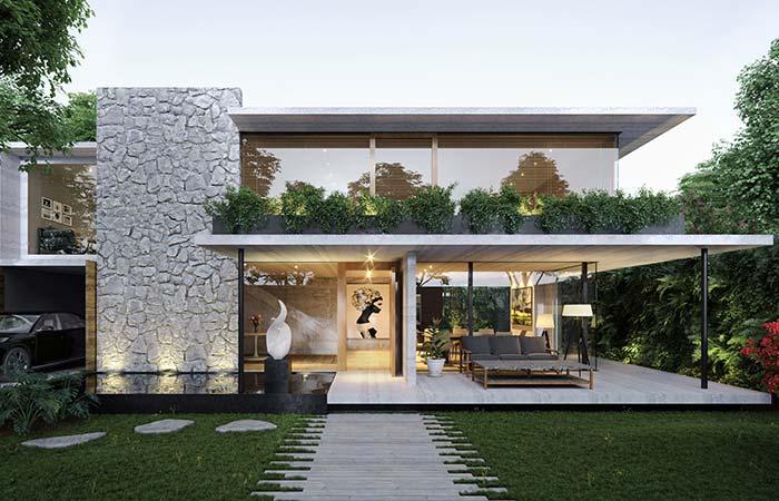 Pedras brancas trazem mais leveza para o conjunto dessa fachada, que conta com o vidro como principal elemento